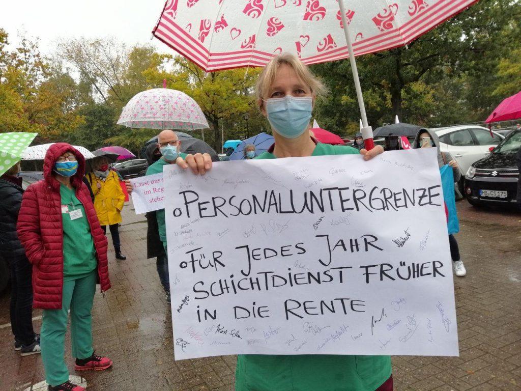 Pflegerin mit Schild: Personaluntergrenze, Für jedes Jahr Schichtdienst früher in die Rente